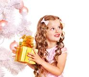 Child with gift box near white Christmas tree. Isolated royalty free stock photo