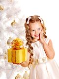 Child with gift box near white Christmas tree. Royalty Free Stock Images