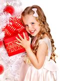 Child with gift box near white Christmas tree. Royalty Free Stock Photos