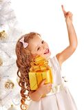 Child with gift box near white Christmas tree. Isolated Stock Images