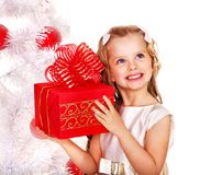 Child with gift box near white Christmas tree. Stock Image