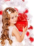 Child with gift box near white Christmas tree. Stock Photos