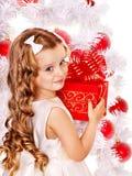 Child with gift box near white Christmas tree. Stock Photos