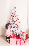 Child with gift box near white Christmas tree Royalty Free Stock Image
