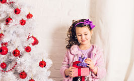 Child with gift box near white Christmas tree Royalty Free Stock Photography