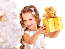Child with gift box near white Christmas tree. Stock Photo