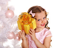 Child with gift box near white Christmas tree. Royalty Free Stock Photography