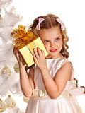 Child with gift box near white Christmas tree. royalty free stock image