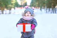 Child with gift box outdoors in winter Stock Image