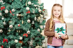 Child with gift at christmas tree. Happy child standing with gift near a christmas tree royalty free stock photo