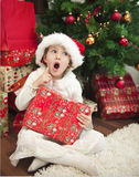 Child with gift in front of christmas tree Royalty Free Stock Photos