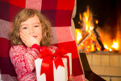 Child with gift near fireplace Stock Image