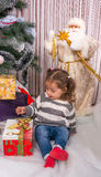 A child with a gifts the Christmas tree. Royalty Free Stock Images