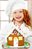 Child with Gingerbread House at Christmas as Chef Royalty Free Stock Photography