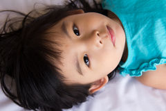 Child girl. Portrait of the little girl laying on bed Royalty Free Stock Photography