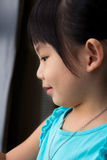 Child girl. Portrait of the little girl stands near by a window Stock Photos