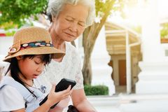 Child girl is addictive, have an elderly grandmother sit royalty free stock image