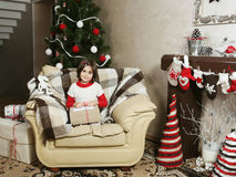 Child Girl on Armchair with Christmas Gift Royalty Free Stock Photo