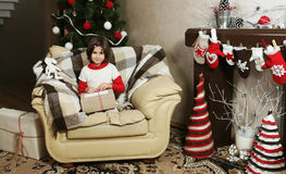 Child Girl on Armchair with Christmas Gift Stock Photo