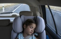 Child girl asleep in a child safety seat in a car. Natural light stock image