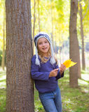 Child girl in autumn poplar forest yellow fall leaves in hand Stock Photos