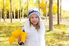 Child girl in autumn poplar forest yellow fall leaves in hand. Child girl in autumn poplar forest with yellow fall leaves in hand smiling happy outdoor Royalty Free Stock Photography