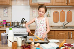 Child girl baking cookies in home kitchen. Raw food and fruits. Healthy food concept. Royalty Free Stock Photography