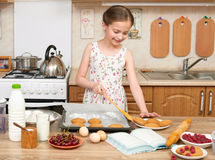Child girl baking cookies in home kitchen. Raw food and fruits. Healthy food concept. Stock Photos