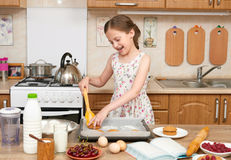 Child girl baking cookies in home kitchen. Raw food and fruits. Healthy food concept. Stock Photo