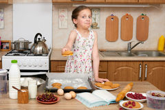 Child girl baking cookies in home kitchen. Raw food and fruits. Healthy food concept. Royalty Free Stock Photo