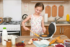 Child girl baking waffles in home kitchen. Raw food and fruits. Healthy food concept. Stock Images
