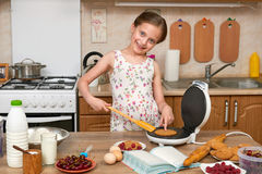 Child girl baking waffles in home kitchen. Raw food and fruits. Healthy food concept. Stock Photos