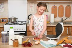 Child girl baking waffles in home kitchen. Raw food and fruits. Healthy food concept. Stock Image
