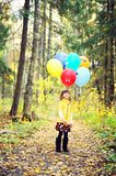 Child girl with balloons in autumn forest Stock Images
