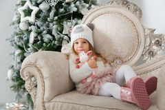 Child girl in bear hat with sheep toy sitting on background of C Royalty Free Stock Image