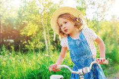 Child girl with bicycle on country road Royalty Free Stock Images