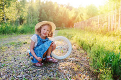 Child girl with bicycle on country road Royalty Free Stock Image