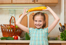 Child girl with big cabbage, vegetables and fresh fruits in kitchen interior, healthy food concept Royalty Free Stock Photos