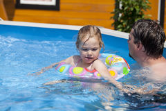 Child girl in bikini bathing in the pool with his father. Little girl in bikini bathing in the pool with his father Royalty Free Stock Photos