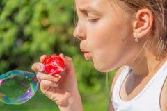 Child girl blowing bubbles. In garden closeup stock photos