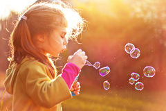 Child girl blowing soap bubbles outdoor. Five years old caucasian child girl blowing soap bubbles outdoor at sunset stock photo
