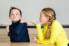 Child girl blows hand kiss to brother Stock Photos