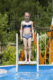 Child girl in blue bikini near swimming pool. Hot Summer. Happy little Girl in blue bikini swimming pool Stock Photos