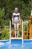 Child girl in blue bikini near swimming pool. Hot Summer Stock Photos