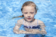 Child girl in blue bikini near swimming pool. Hot Summer. Happy little Girl in blue bikini swimming pool Royalty Free Stock Images