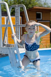 Child girl in blue bikini near swimming pool. Hot Summer. Happy little Girl in blue bikini swimming pool Stock Photo