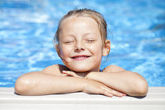 Child girl in blue bikini near swimming pool. Hot Summer. Happy little Girl in blue bikini swimming pool Stock Image
