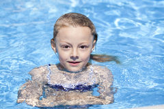 Child girl in blue bikini near swimming pool. Hot Summer Stock Image