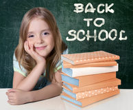 Child girl with books on blackboard background. Royalty Free Stock Images