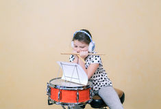 Child girl boring by sitting and learn a drum scores Royalty Free Stock Photography